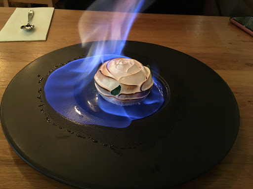 A rose-shaped dessert set on fire with a blue flame