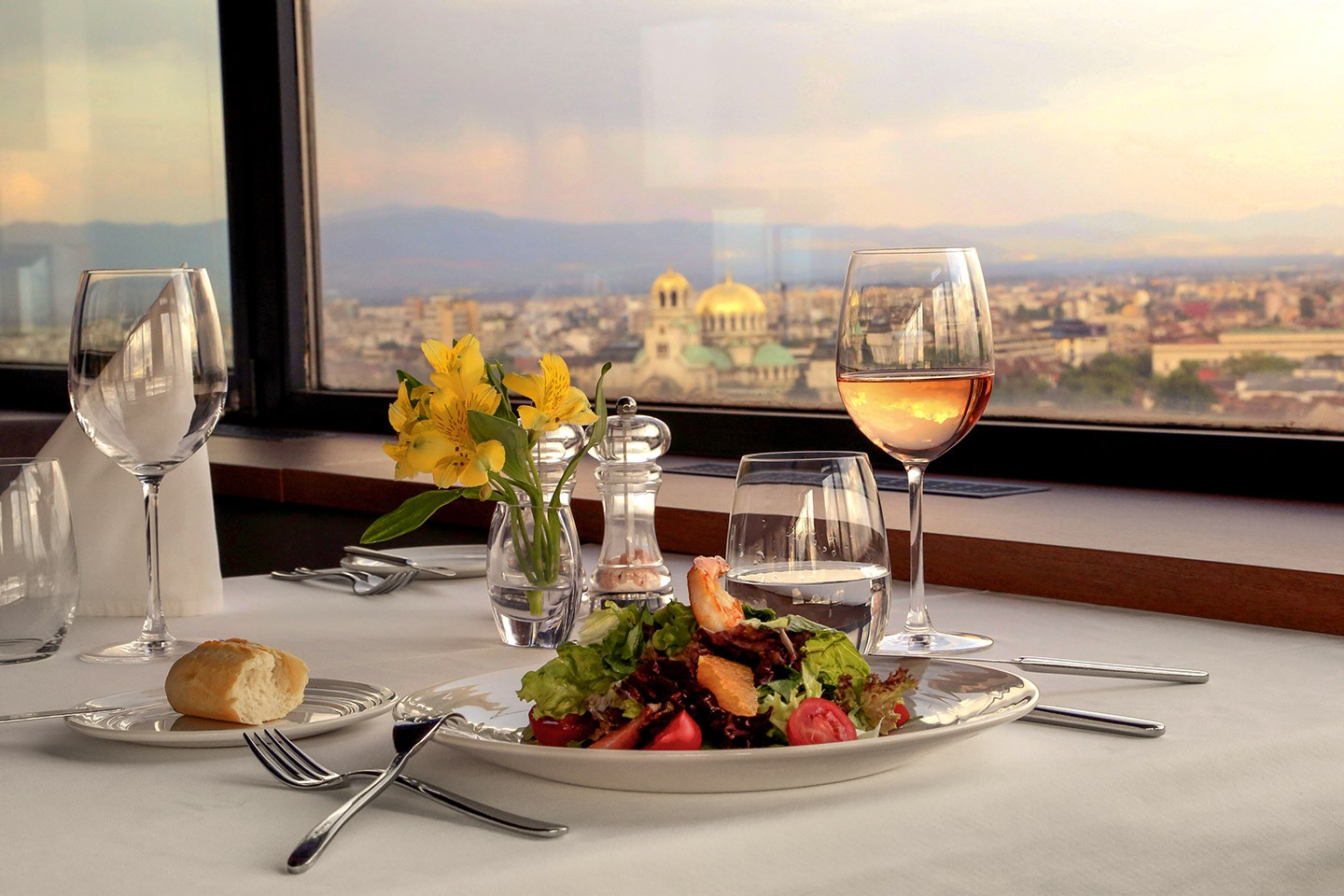 Food and wine at a restaurant in the foreground and a view of the city Sofia in the background